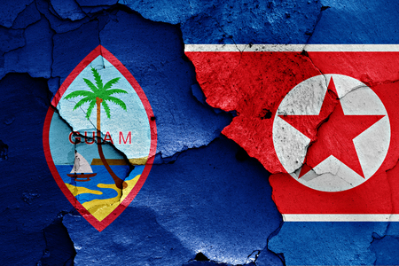 Flag of Guam and North Korea painted on cracked wall