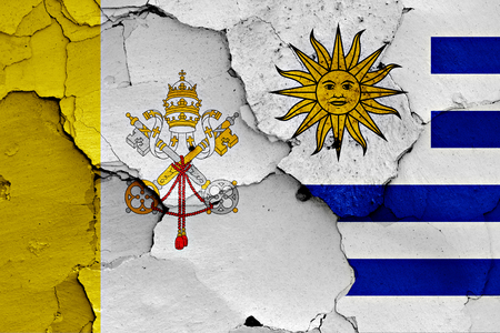 flag of Vatican and Uruguay painted on cracked wall