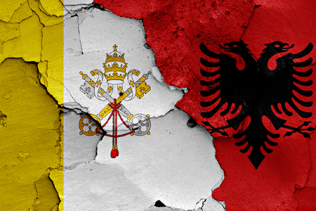flag of Vatican and Albania painted on cracked wall