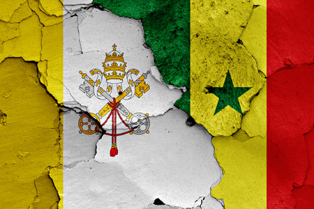 flag of Vatican and Senegal painted on cracked wall Stock Photo