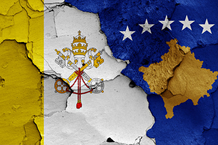 flag of Vatican and Kosovo painted on cracked wall Stock Photo