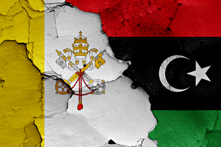 flag of Vatican and Libya painted on cracked wall Stock Photo