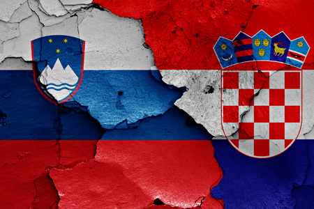 flags of Slovenia and Croatia painted on cracked wall 写真素材