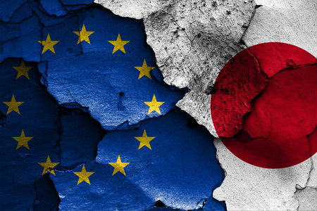 flags of European union and Japan painted on cracked wall