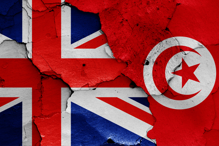 flags of UK and Tunisia painted on cracked wall 版權商用圖片
