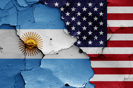 flags of Argentina and USA painted on cracked wall Foto de archivo