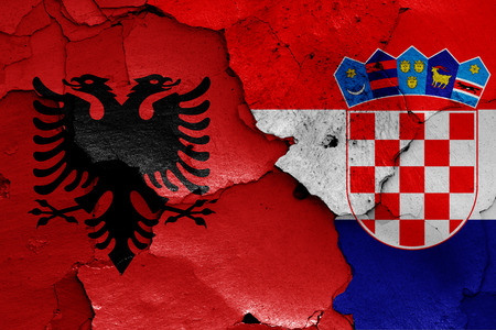 flags of Albania and Croatia painted on cracked wall