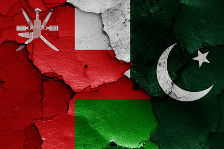 flags of Oman and Pakistan painted on cracked wall
