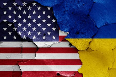 flags of USA and Ukraine painted on cracked wall