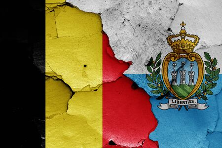 flags of Belgium and San Marino painted on cracked wall