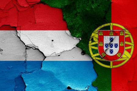 flags of Luxembourg and Portugal painted on cracked wall Stok Fotoğraf - 131191166
