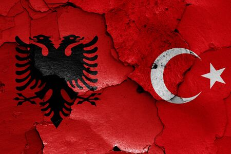 flags of Albania and Turkey painted on cracked wall