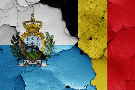 flags of San Marino and Belgium painted on cracked wall