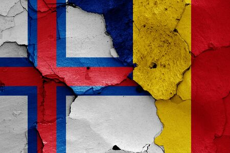 flags of Faroe Islands and Romania painted on cracked wall 写真素材