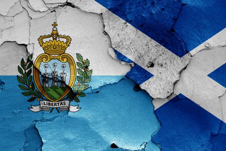 flags of San Marino and Scotland painted on cracked wall