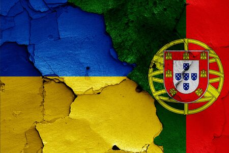 flags of Ukraine and Portugal painted on cracked wall