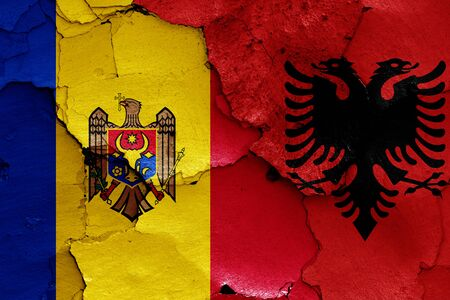 flags of Moldova and Albania painted on cracked wall