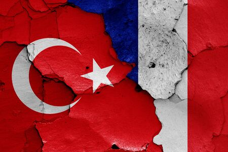flags of Turkey and France painted on cracked wall