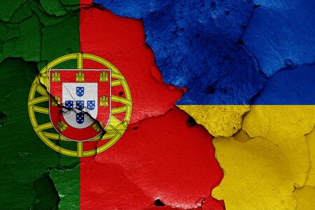 flags of Portugal and Ukraine painted on cracked wall