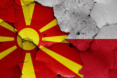 flags of North Macedonia and Poland painted on cracked wall Stockfoto
