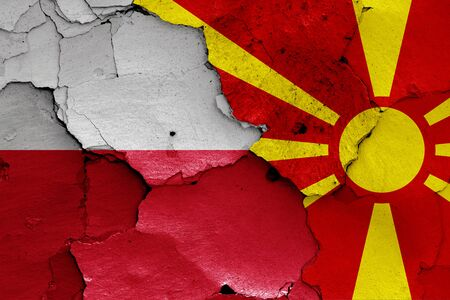 flags of Poland and North Macedonia painted on cracked wall