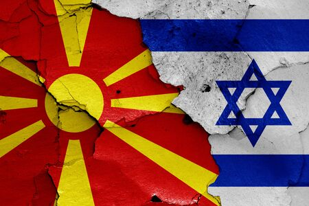 flags of North Macedonia and Israel painted on cracked wall
