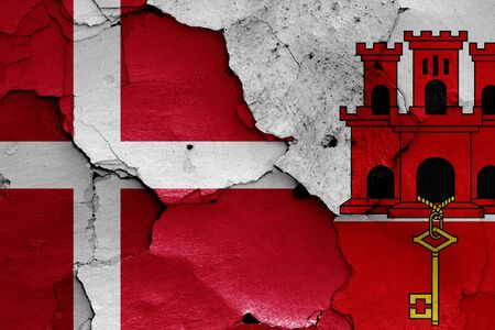 flags of Denmark and Gibraltar painted on cracked wall Stok Fotoğraf