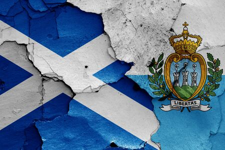 flags of Scotland and San Marino painted on cracked wall