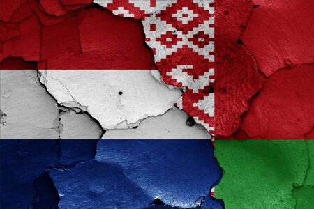 flags of Netherlands and Belarus painted on cracked wall