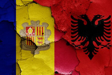flags of Andorra and Albania painted on cracked wall