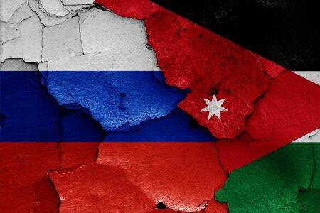 flags of Russia and Jordan painted on cracked wall