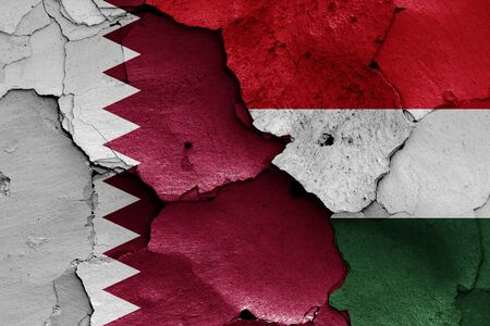 flags of Qatar and Hungary painted on cracked wall
