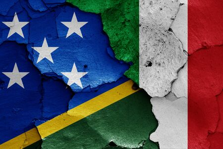 flags of Solomon Islands and Italy painted on cracked wall