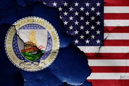 flags of Department of Agriculture and USA painted on cracked wall 写真素材
