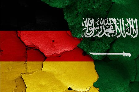 flags of Germany and Saudi Arabia painted on cracked wall Stock Photo