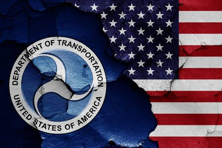 flags of Department of Transportation and USA painted on cracked wall Foto de archivo