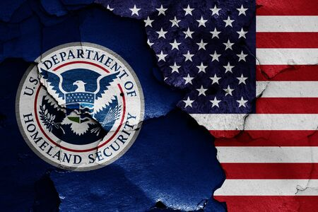flags of Department of Homeland Security and USA painted on cracked wall