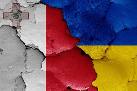 flags of Malta and Ukraine painted on cracked wall 스톡 콘텐츠