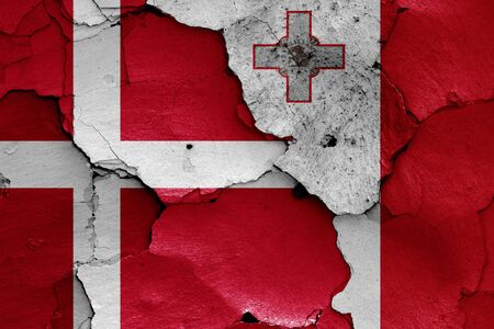 flags of Denmark and Malta painted on cracked wall 스톡 콘텐츠
