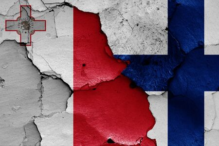 flags of Malta and Finland painted on cracked wall 스톡 콘텐츠