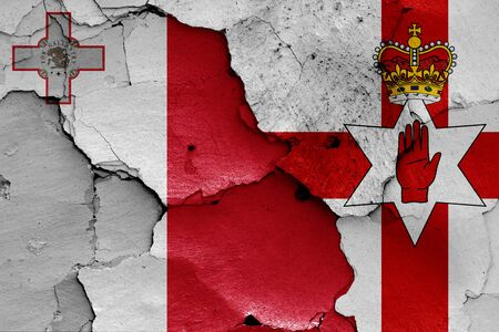 flags of Malta and Northern Ireland painted on cracked wall 스톡 콘텐츠