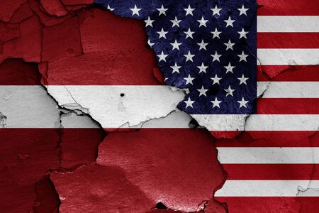 flags of Latvia and USA painted on cracked wall