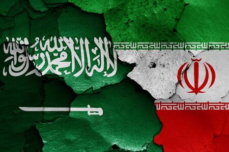 flags of Saudi Arabia and Iran painted on cracked wall