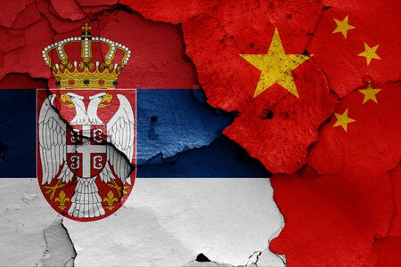 flags of Serbia and China painted on cracked wall