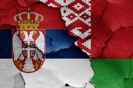 flags of Serbia and Belarus painted on cracked wall Zdjęcie Seryjne