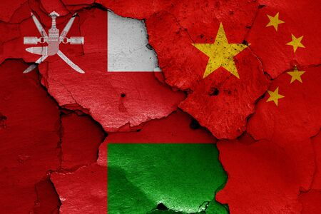 flags of Oman and China painted on cracked wall