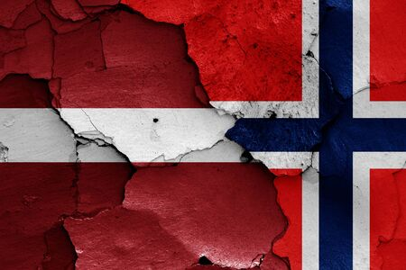 flags of Latvia and Norway painted on cracked wall Zdjęcie Seryjne
