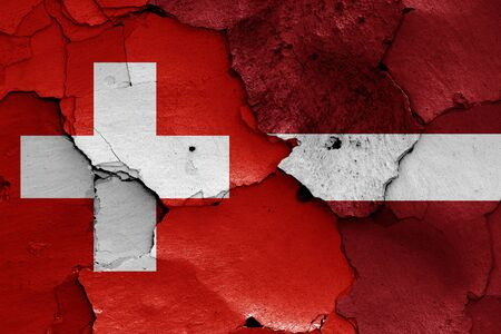 flags of Switzerland and Latvia painted on cracked wall Zdjęcie Seryjne