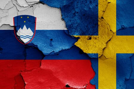flags of Slovenia and Sweden painted on cracked wall