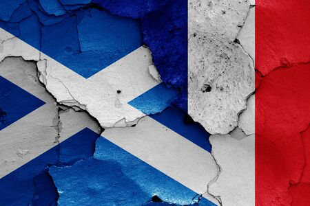 flags of Scotland and France painted on cracked wall
